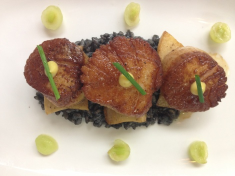 Scallops on a bed of squid ink risotto