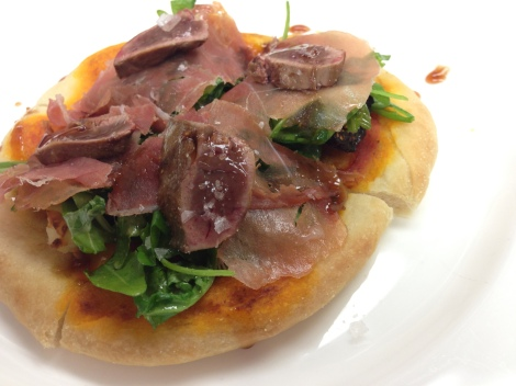 Pizza topped with prosciutto, arugula, and seared duck liver.